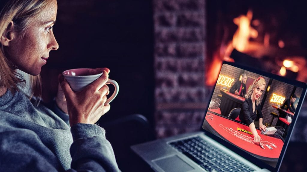 Woman playing on the laptop while drinking tea in Rizk casino
